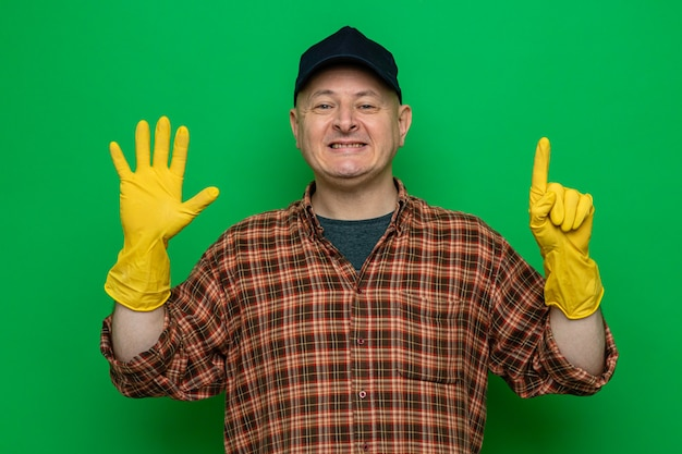 格子縞のシャツとキャップを身に着けている幸せで前向きな掃除人は、指で6番を示して笑顔に見えるゴム手袋を着用しています