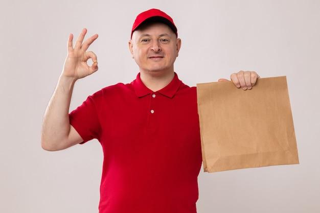 赤い制服を着た幸せで前向きな配達人と紙のパッケージを保持している帽子は元気に笑顔を見てokサイン