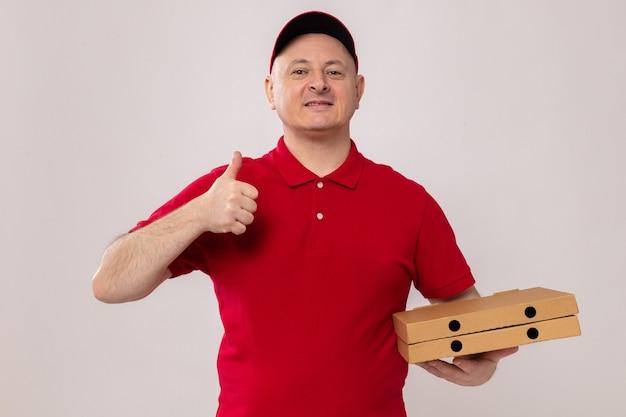Счастливый и позитивный доставщик в красной форме и кепке, держащий коробки для пиццы, улыбается и показывает палец вверх