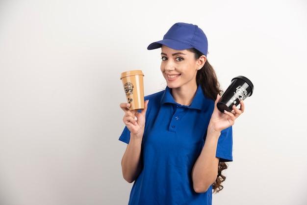 Счастливая и позитивная доставщица с чашками кофе. фото высокого качества