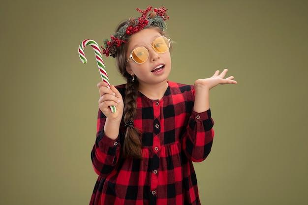 Счастливая и позитивная маленькая девочка в рождественском венке в клетчатом платье держит конфету, весело улыбаясь, стоя у зеленой стены