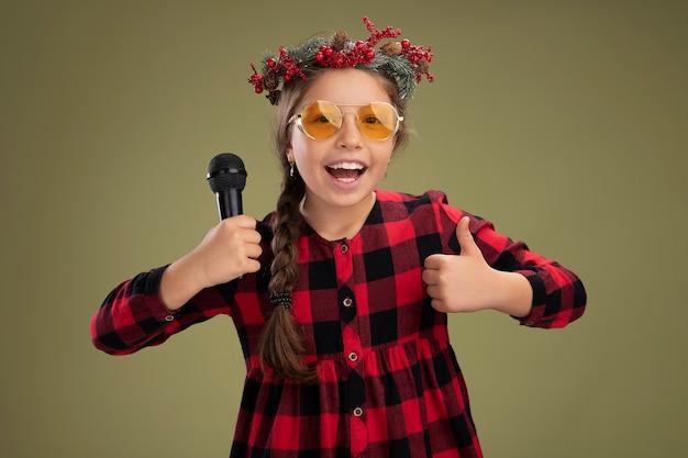 녹색 배경 위에 서 엄지 손가락을 유쾌하게 보여주는 미소 체크 드레스를 들고 마이크를 들고 크리스마스 화환을 입고 행복하고 긍정적 인 어린 소녀