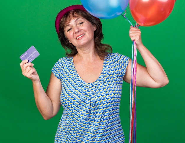 Счастливая и позитивная женщина среднего возраста в праздничной шляпе с разноцветными воздушными шарами и кредитной картой, весело улыбаясь, празднует день рождения, стоя над зеленой стеной