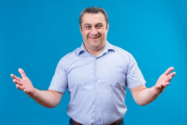 Счастливый и позитивный мужчина средних лет в синей рубашке показывает объятие двумя открытыми руками на синем пространстве