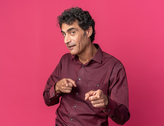 ピンクの上に元気に立って笑顔のカメラに人差し指で指している紫色のシャツの幸せで前向きな年配の男性