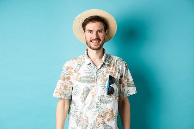 カメラに微笑んで、アロハシャツと麦わら帽子で幸せで前向きな観光客。観光と夏休みの概念。