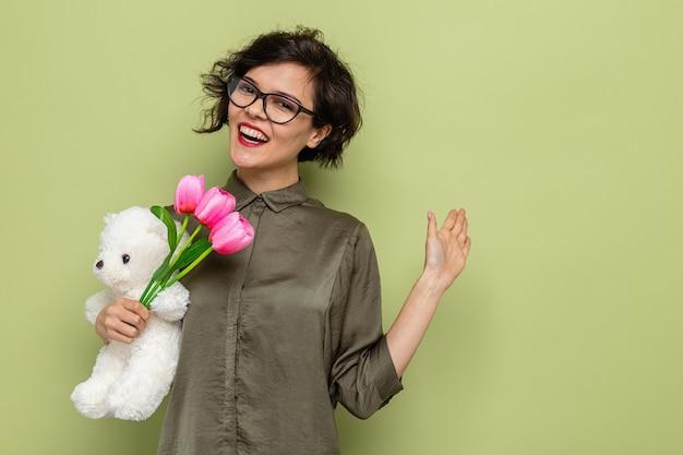 튤립과 테디 베어의 꽃다발을 들고 짧은 머리를 가진 행복하고 긍정적 인 여자는 3 월 8 일 국제 여성의 날을 축하하는 손으로 유쾌하게 흔들며 웃고 카메라를보고