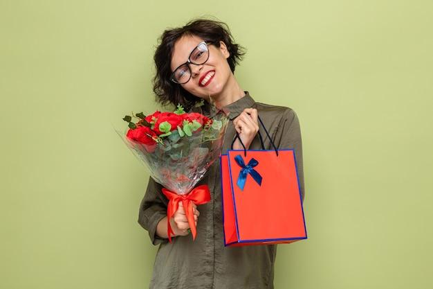국제 여성의 날을 즐겁게 축하하는 선물로 꽃과 종이 봉지를 들고 짧은 머리를 가진 행복하고 긍정적 인 여자