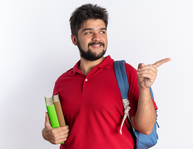 赤いポロシャツを着た幸せでポジティブな若いひげを生やした学生男で、ノートを持ったバックパックが横に人差し指で横に立っている