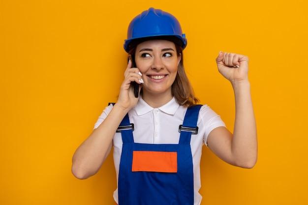 건설 유니폼과 안전 헬멧을 쓴 행복하고 긍정적인 젊은 건축업자 여성이 휴대전화로 통화하는 동안 주먹을 꽉 쥐고 있습니다.