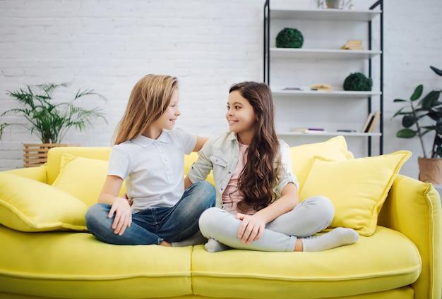 행복하고 긍정적 인 젊은 십대 노란색 소파에 앉아 서로를 봐. 여자는 다리를 건너 유지합니다. 그들은 말했다.