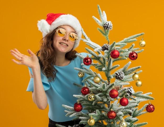 Счастливая и позитивная молодая женщина в синем топе и шляпе санта-клауса в желтых очках, украшающих елку, смотрит в камеру, машет рукой, стоя на оранжевом фоне