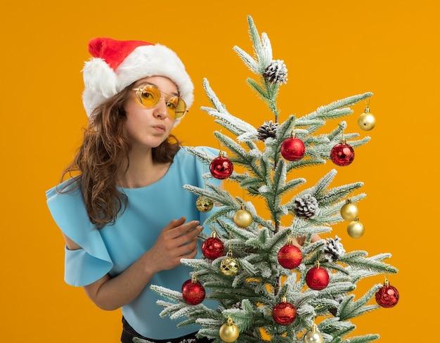 주황색 벽 위에 서있는 크리스마스 트리를 장식하는 노란색 안경을 쓰고 파란색 상단과 산타 모자에 행복하고 긍정적 인 젊은 여자