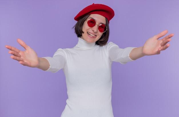 베레모와 빨간 선글라스를 착용하는 흰색 터틀넥에 짧은 머리를 가진 행복하고 긍정적 인 젊은 여성