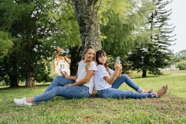 公園で背中合わせに座っている幸せでリラックスした母と娘。