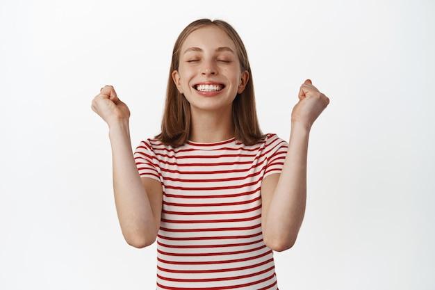 勝利から喜び、目標を達成し、結果に満足し、目を閉じてガッツポーズ、白い歯を笑顔、勝利、勝利を祝う、達成、白い壁、幸せで安心した金髪の女性。