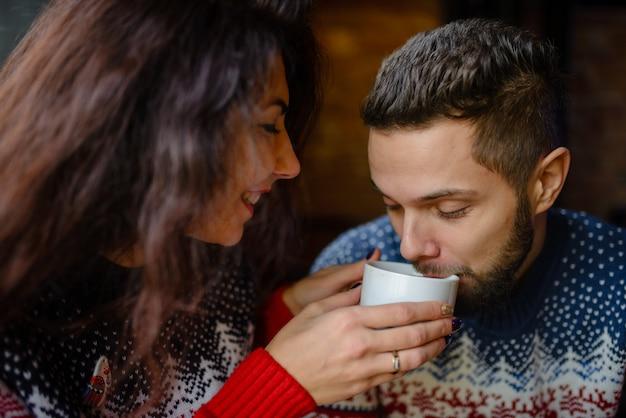 Счастливые и романтичные пары в теплых свитерах пьют кофе из одноразовых бумажных стаканчиков в кафетерии.