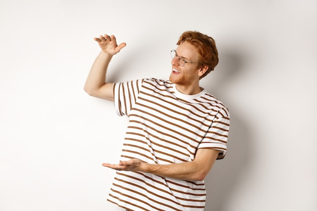 幸せで満足している白人の赤毛の男は、大きな製品を示し、満足している、白い背景を笑顔で、何か大きなものを紹介します