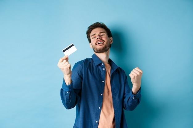 행복 하 고 만족 젊은 남자 플라스틱 신용 카드, 주먹 펌프와 미소, 파란색 배경에 서있는 춤.