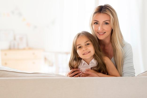 幸せで笑顔の若い母と娘が一緒にポーズをとる