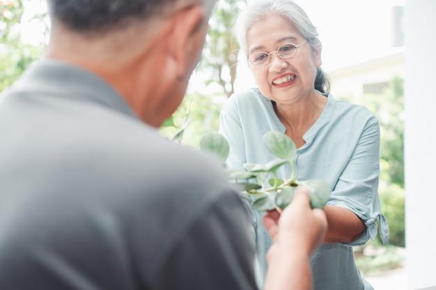 Счастливая и улыбающаяся азиатская старая пожилая женщина предлагает цветок