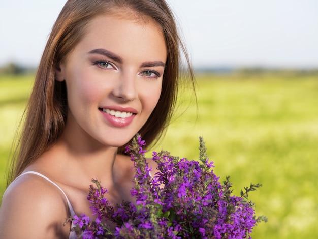 手に紫色の花を持つ屋外の幸せで笑顔の美しい女性。若い陽気な女の子は、春の野原で自然にいます。自由の概念。牧草地の可愛くてセクシーなモデルの肖像画