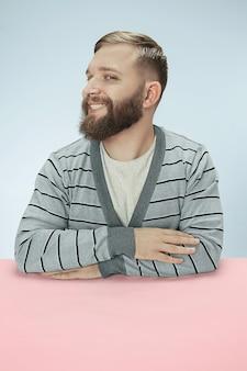 青いスタジオの背景にテーブルに座って幸せで笑顔のビジネスマン。ミニマリズムスタイルの肖像画