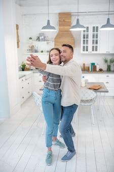 幸せで笑顔のお父さんと娘が自宅のキッチンで踊っています。