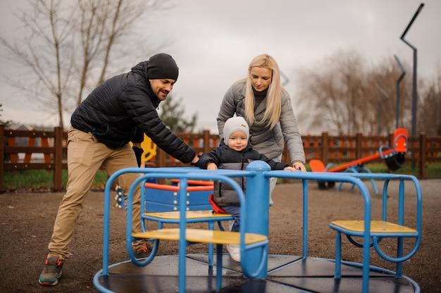カルーセルに乗って幼い息子と幸せと笑顔の家族カップル