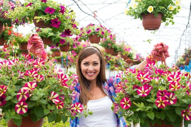 温室ガーデンセンターで花束の花の植物を保持している幸せで笑顔の女性の花屋