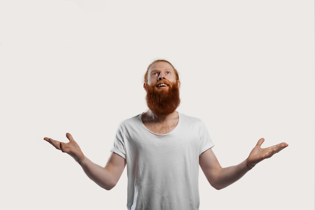 白いtシャツを着た幸せで笑顔の男が賞を受賞し、腕を開きます