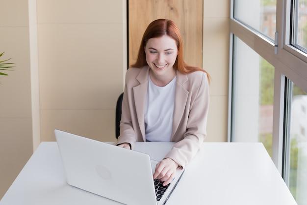 家に座ってコンピューターで働く幸せで笑顔の赤毛のビジネス女性