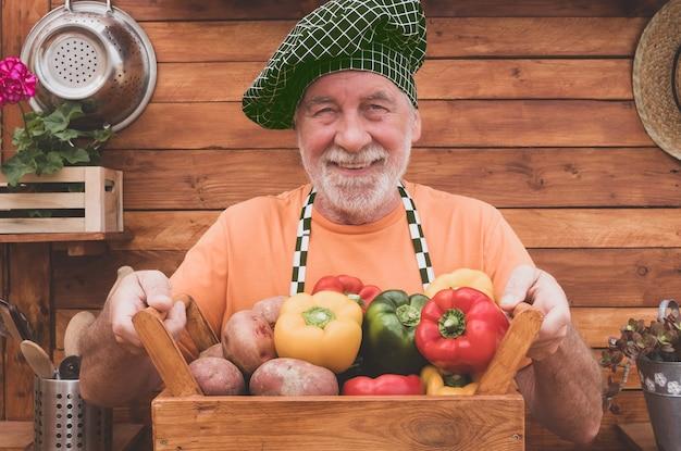 庭から採れたてのピーマンとジャガイモでいっぱいの木製バスケットを見せて幸せで笑顔のシニア農家