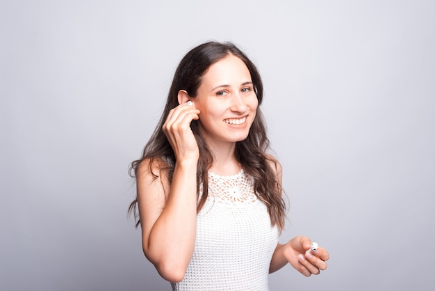 イヤポッドを使用して、白い壁に自信を持って見える幸せで笑顔の女性