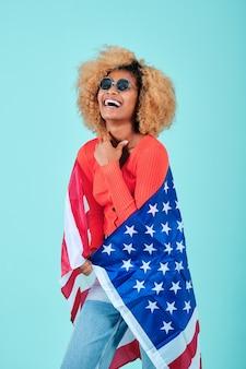 Счастливая и улыбающаяся молодая афро женщина, держащая флаг сша на изолированном фоне. концепция празднования дня независимости сша.