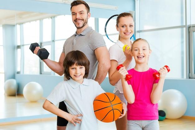 幸せでスポーティー。ヘルスクラブで互いに近くに立っている間、さまざまなスポーツ用品を持っている幸せな家族