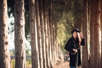Happy and stylish hipster woman taking photo with photo camera on background of Pine tree