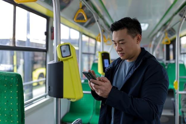 公共交通機関で幸せで成功したアジア人男性の乗客は、笑顔でカメラを見ながら携帯電話を使用してチケットを購入しました