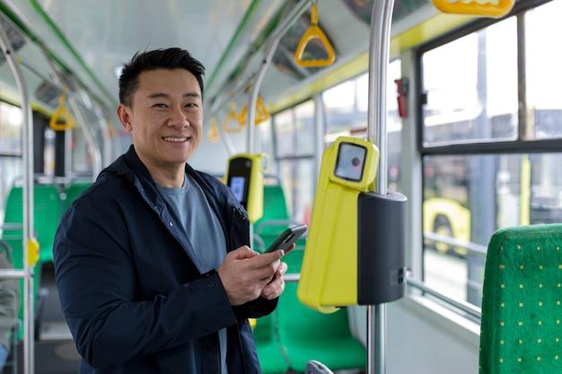 대중 교통에서 행복하고 성공적인 아시아 남성 승객은 미소를 지으며 카메라를 보며 휴대폰을 사용하여 티켓을 샀습니다.