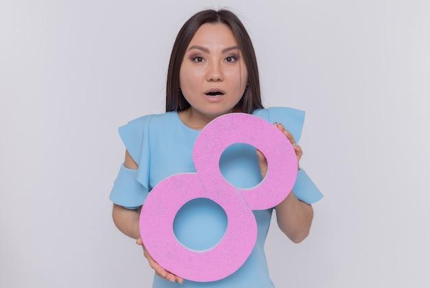 카메라를보고 골판지로 만든 번호 8을 들고 행복하고 놀란 아시아 여자