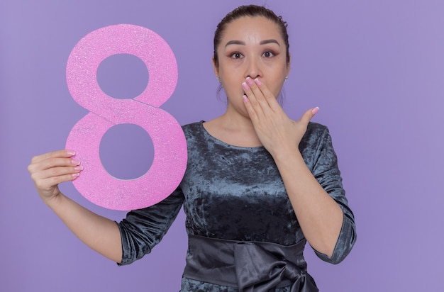 段ボールで作られた8番を保持している幸せで驚きのアジアの女性