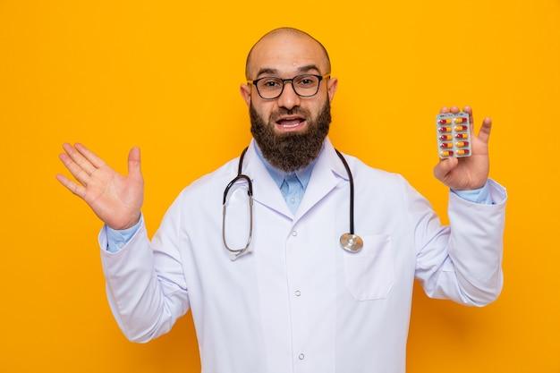 흰색 코트에 행복하고 놀란 수염 난 남자 의사가 팔을 제기 유쾌하게 웃고있는 약을 들고 안경을 쓰고 안경을 쓰고 청진기를 쓴다.