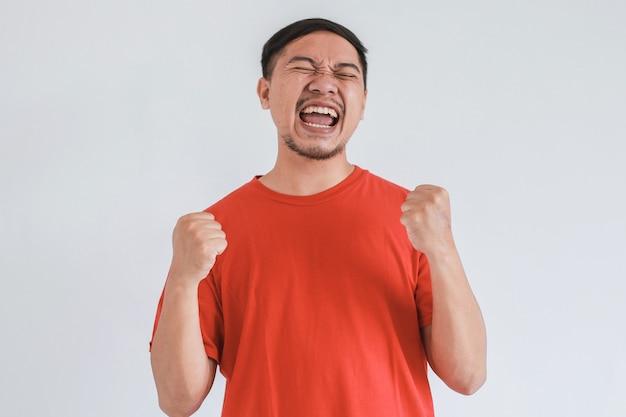Счастливое и удивленное выражение лица для победы чего-то азиатского мужчины в красной футболке на белом фоне