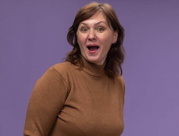 보라색 벽 위에 넓게 서있는 갈색 터틀넥에 행복하고 놀란 중간 나이 든 여자