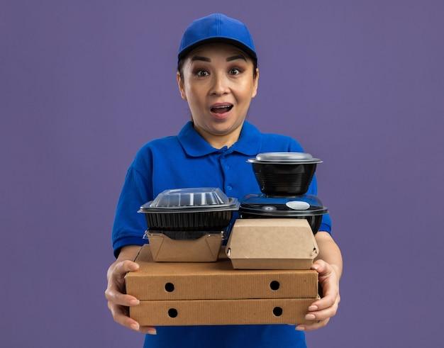 파란색 유니폼과 보라색 벽 위에 서있는 피자 상자와 음식 패키지를 들고 모자에 행복하고 놀란 젊은 배달 여자