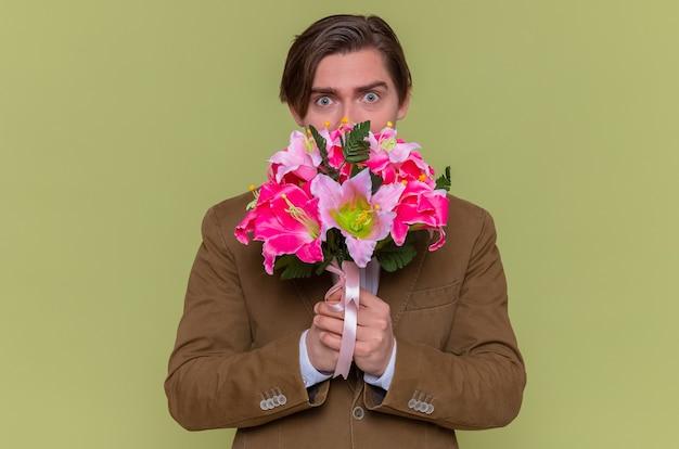 유쾌하게 웃는 꽃의 꽃다발을 들고 행복하고 놀란 젊은 남자 무료 사진