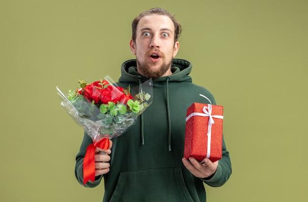 꽃 부케와 캐주얼 옷에 행복하고 놀란 젊은 남자와 녹색 배경 발렌타인 데이 개념 위에 서 그의 여자 친구를위한 선물