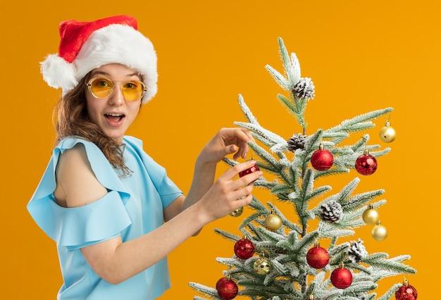 青いトップとオレンジ色の背景の上に立っているクリスマスツリーを飾る黄色いメガネをかけているサンタ帽子の幸せで驚きの若い女性
