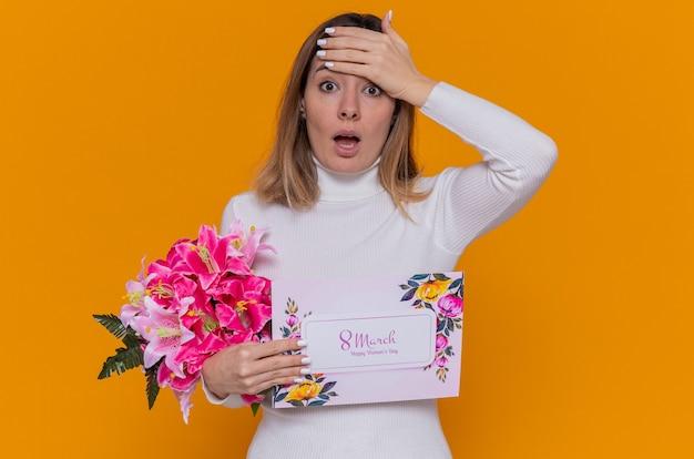 인사말 카드와 꽃의 꽃다발을 들고 흰색 터틀넥에 행복하고 놀란 젊은 여자