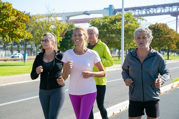행복하고 피곤한 성숙한 조깅하는 사람들은 야외에서 달리기, 마라톤 훈련, 아침 운동 즐기기. 은퇴 한 사람과 활동적인 라이프 스타일 컨셉